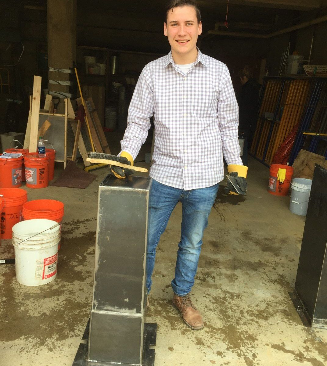 A student poses next to one of our two metal water filter molds.